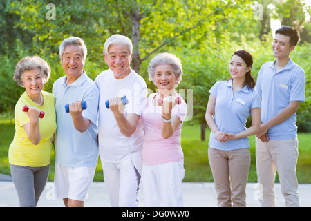 Seniors  exercising with dumbbell in nursing home - Stock Photo