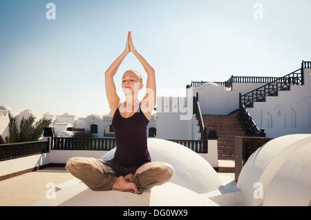 Attractive redhair woman practicing Vinyasa yoga outdoors - Stock Photo