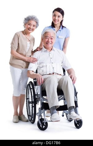 Wheelchair bound man with his wife and nursing assistant - Stock Photo