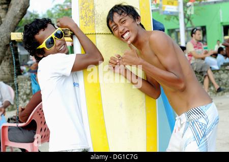 young Indonesian men on Kuta beach, Bali, Indonesia - Stock Photo