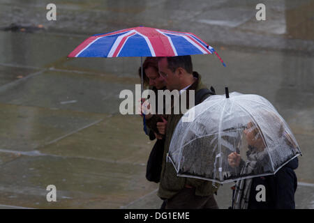 Trafalgar Square London,UK. 11th Oct, 2013.  Members of the public shelter under umbrellas on a wet rainy day in - Stock Photo