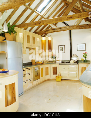 Ceramic tiled floor and large refrigerator in contemporary barn conversion kitchen with beamed apex ceiling and cream Aga