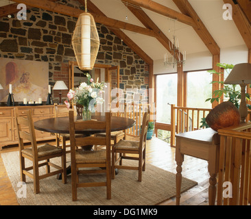 Cylindrical light above circular mahogany dining table and rush-seated chairs in upstairs dining room with exposed - Stock Photo