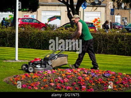 Council gardener mowing lawn in Hall Leys Park in Matlock Derbyshire England UK an award winning park in the Peak - Stock Photo