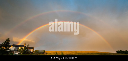 Double rainbow at sunset, against a cloudy sky over a Northumbrian dale. - Stock Photo