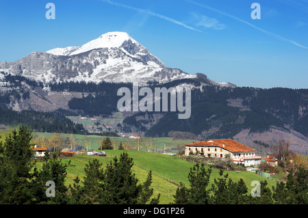 village in Aramaio valley, surrounding by snowy mountains, in Basque Country - Stock Photo