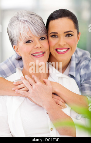 loving daughter hugging middle aged mother at home - Stock Photo