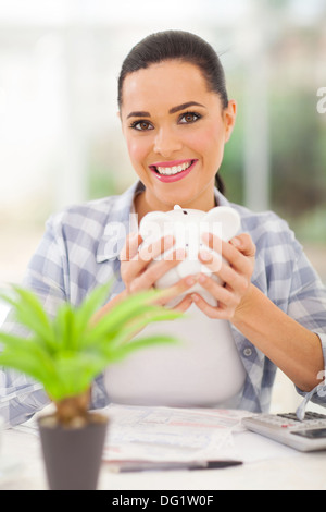 happy young woman holding piggyback and calculating savings - Stock Photo