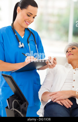 beautiful healthcare worker doing senior patient's checkup in office - Stock Photo