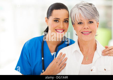 portrait of middle aged woman and medical nurse - Stock Photo