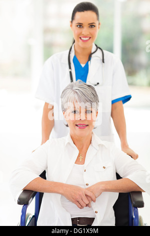friendly medical nurse taking care of senior patient in wheelchair - Stock Photo