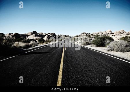 Remote Road Lined with Rock Outcroppings, Joshua Tree National Park, California, USA - Stock Photo