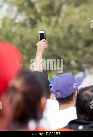 Man using an iPhone to video tape an outdoor event over crowd of people - Stock Photo