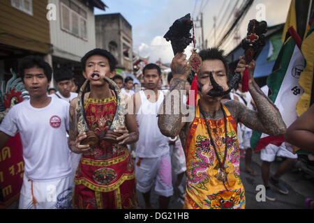 Phuket, Thailand. 12th Oct, 2013. Devotees walk in a procession outside the Kathu Chinese Shrine during a street - Stock Photo