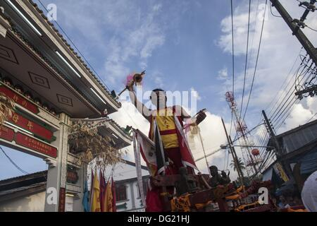 Phuket, Thailand. 12th Oct, 2013. A devotee rides atop a shrine with Chinese Emperor Gods outside the Kathu Chinese - Stock Photo