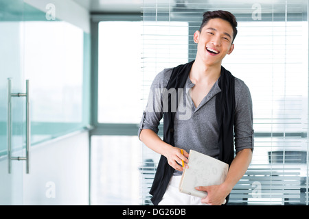 Young businesswoman with laptop in the office - Stock Photo