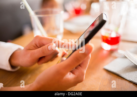 Female message sms mobile phone cafe - Stock Photo
