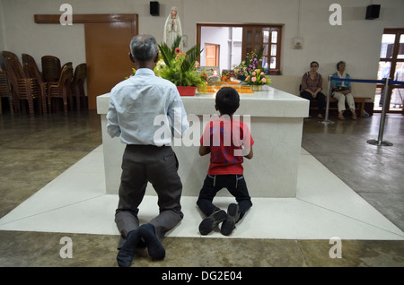 Visitors praying on the tomb of Mother Teresa in Mother House, Kolkata, India - Stock Photo