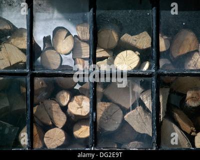 Logs in storage,seen through a window - Stock Photo