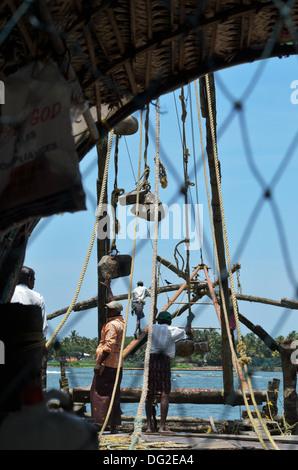 Fishermen working on Chinese Fishing Nets, Fort Kochi - Stock Photo