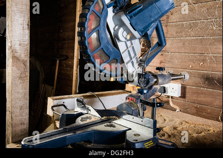 A sliding compound mitre saw, in a workshop. - Stock Photo