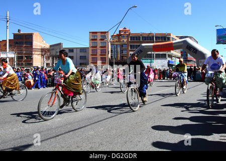El Alto, Bolivia. 12th Oct, 2013.  A competitor rides past spectactors as she takes part in a Cholitas Bicycle Race - Stock Photo
