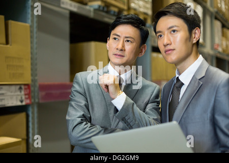 Business partners with laptop in logistic warehouse - Stock Photo