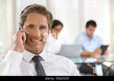 Male mobile phone office desk looking camera - Stock Photo