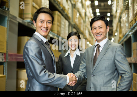 Business people shaking hands in warehouse - Stock Photo