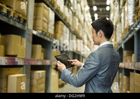 Businessman using digital tablet in warehouse - Stock Photo