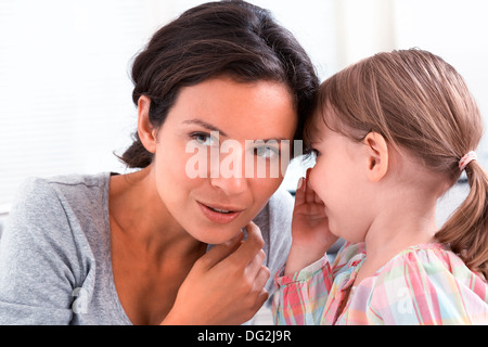 Happy mother with her daughter saying a secret in doors - Stock Photo