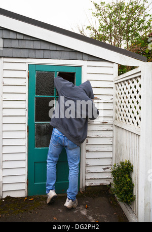 A suspicious person, man wearing a hooded jacket breaking into a garden shed or garage. - Stock Photo