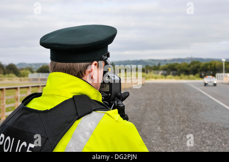 Police officer uses a Laser Technology Inc UltraLyte laser speed detector gun - Stock Photo