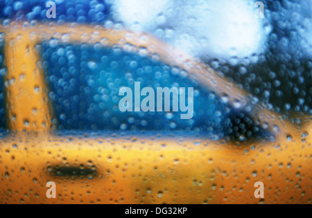 Blurry view of a New York City taxi seen through window covered in rain drops. - Stock Photo