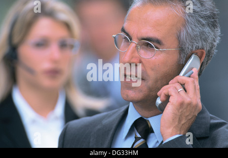 Two executives talking on cell phones - Stock Photo