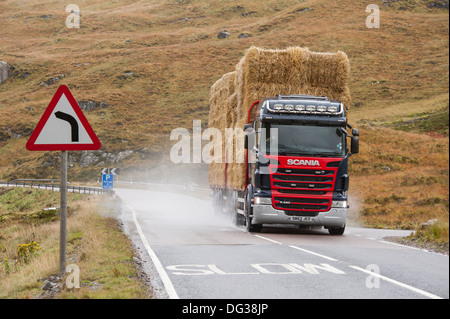 A heavy goods vehicle articulated lorry carrying straw bales along a dangerous mountainous road  at glencoe showing - Stock Photo