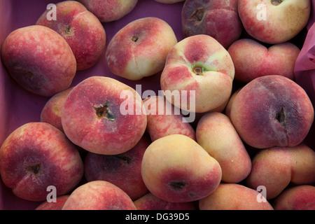 Saturn peaches or Donut (Doughnut) peaches, Prunus persica var. platycarpa, at a market stall, Hanover, Lower Saxony, - Stock Photo
