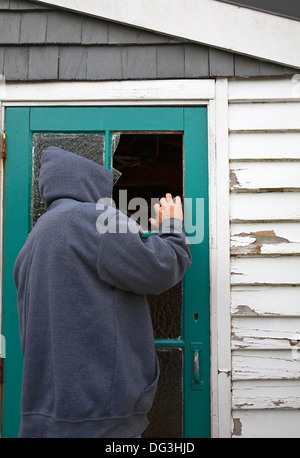 A suspicious person, man wearing a hooded jacket peering through a broken window pane in a door of a garden shed. - Stock Photo