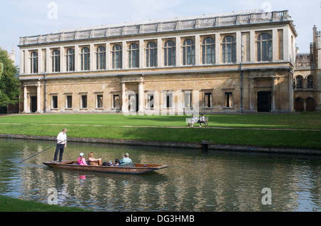 Punt with tourists passing the Wren library of Trinity College University of Cambridge, England, UK - Stock Photo