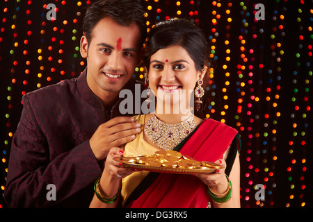 Happy Indian Couple showing gold coins on Diwali Festival - Stock Photo