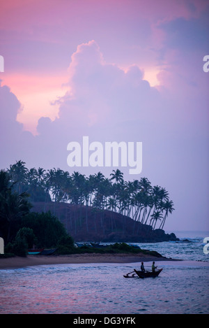 Mirissa Beach, traditional Sri Lankan outrigger fishing boat at sunrise, South Coast, Southern Province, Sri Lanka, - Stock Photo