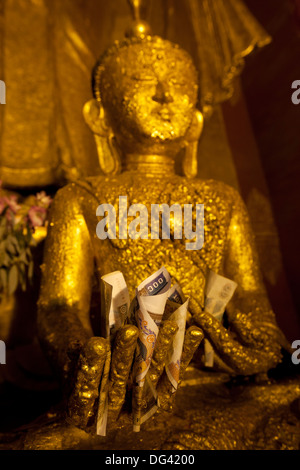 Gold Buddha with money offering in hand, Bagan, Central Myanmar, Myanmar - Stock Photo