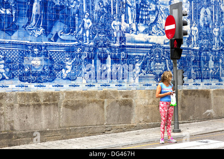 Young woman in front of blue azulejo tiling covering wall of Capela das Almas, town centre, Porto, Portugal - Stock Photo