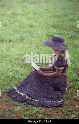 a woman in a romantic dress is sitting on a lawn, reading a book - Stock Photo
