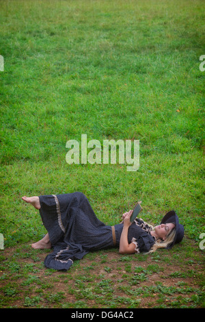 a woman in a romantic dress is lying on a meadow, reading a book - Stock Photo