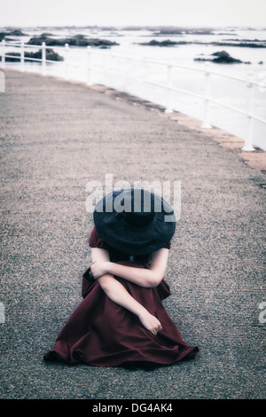 a woman in a red dress with a black sunhat is sitting on a pier - Stock Photo