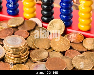 A bunch of various Euro coins and cents in front of an abacus - Stock Photo