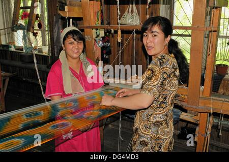 silk production, usbek woman working on a wooden loom, Silk Road, Fergana Valley, Uzbekistan, Central Asia - Stock Photo