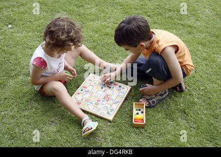 6 year old children playing the goose game - Stock Photo