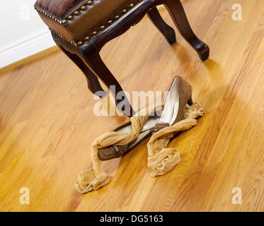 Angled photo of woman stockings and dress shoes lying next to padded footstool with red oak floors in background - Stock Photo